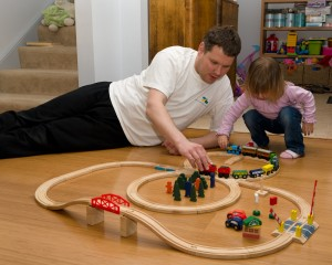 Tim and Anastasia playing with her (their?) train set